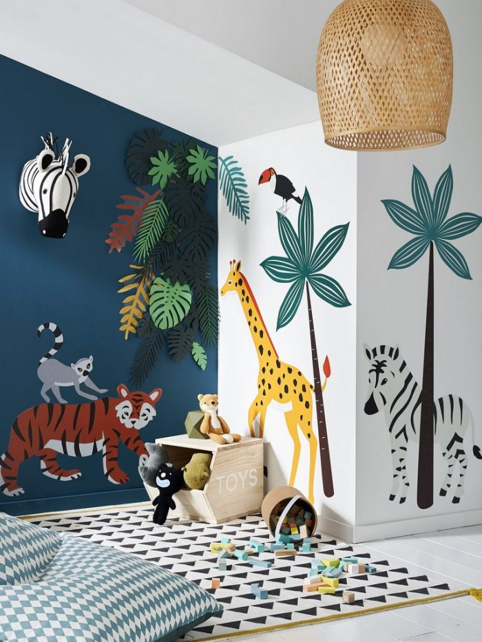 kids room, white floor, white wall, animals stickers on the wall, stuffed animals, zebra head decorations, rattan pendant, bean bag, white rug