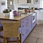 Kitchen, Brown Rough Tiles On Floor, White Wall, White Cabinet, Light Purple Sialnd With Cabinet And Wooden Top, Rattan Back Stools With Purple Seating