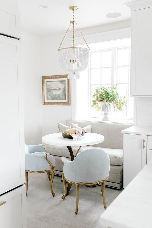kitchen corner nook, white sofa, blue classic chairs, white round table, white fringe chandelier