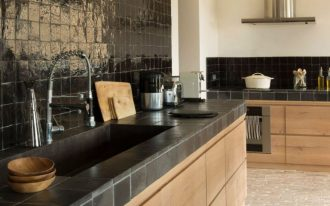 kitchen, open brick floor tiles, wooden cabinet, blak tiles kitchen top, black backsplash tiles, black sconces, beige wall, hood