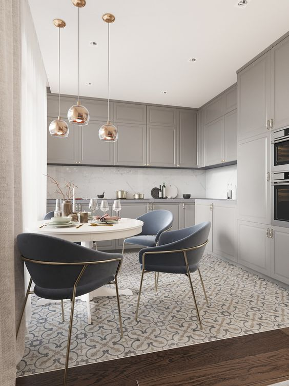 kitchen, patterned floor, veige upper and bottom cabinet, marble backsplash, white tulip table, dark grey chairs with golden metal support, golden pendants
