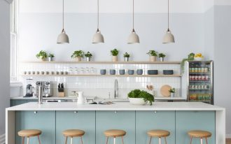 kitchen with modern island bar, white backsplash tiles, white tiles, pastel blue kitchen cabinet and island with white top, white pendants