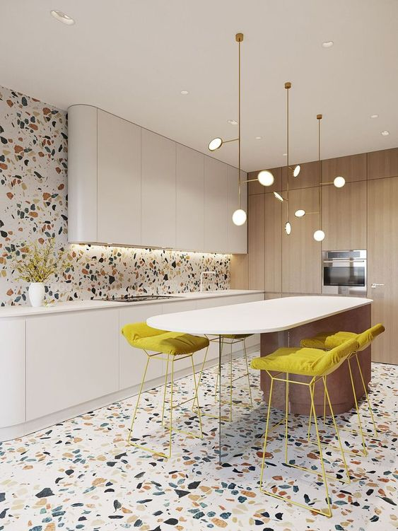 kitchen with terrazzo tiles ont he floor and wall, white upper cabinet, white bottom cabinet, white smooth island with yellows cushion stools, wooden large cabinet pantry