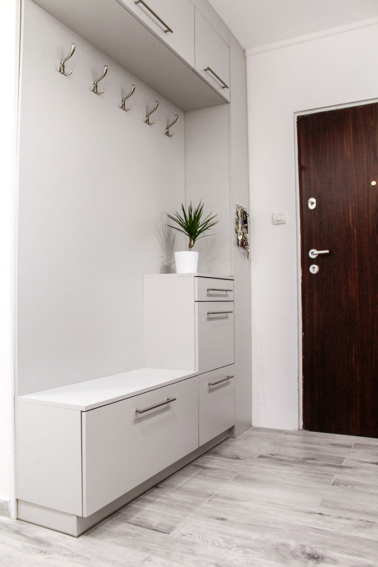 light grey built in entrance with cabinet stacked at the bottom, storage on top, hooks on the nook