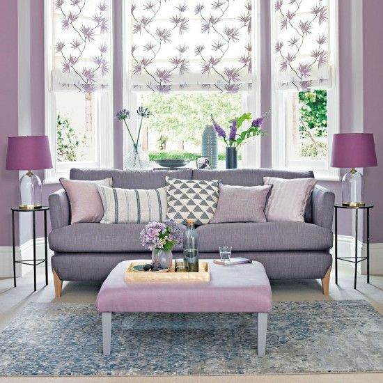 living room in the alcove, large windows, white purple roman shade, purple sofa, purple ottoman, purple table lamp, side table, grey rug