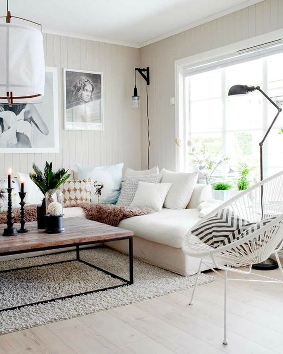 living room, light wooden floor, rug, white cornered sofa, wooden table, white rattan chair, white plank wall, black floor lamp, white paper pendant