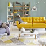 Living Room, White Wooden Floor, Green Wall, Yellow Sofa, Grey Chair, Silver Curvy Floor Lamp, Shelves, White Coffee Table