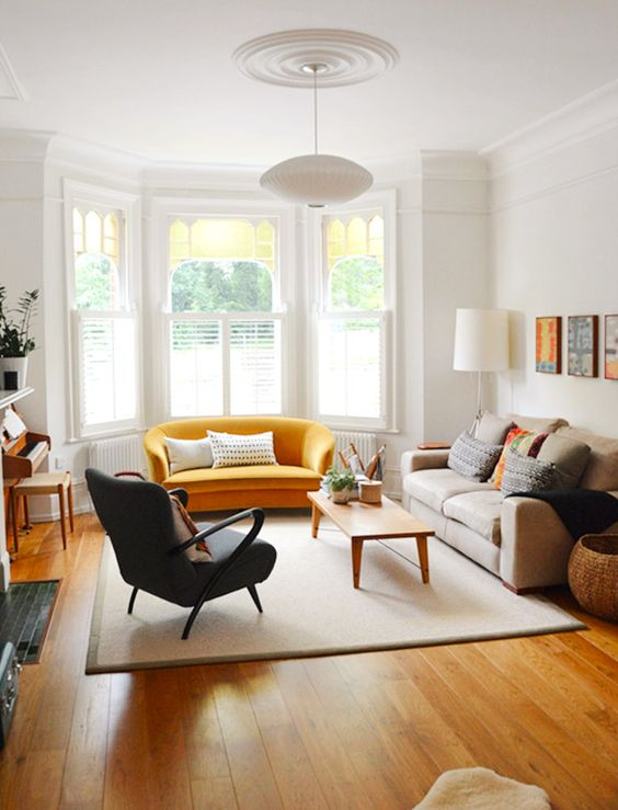 living room, wooden floor, brown rug, yellow sofa, brown sofa, black chair, wooden coffee table, white wall, windows on alcove, white floor lamp, white pendant