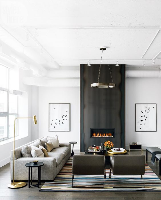 living room, wooden floor, white wall, black wall on fire place, grey sofa, beige chairs, black squre coffee table, stools, rug, golden floor lamp