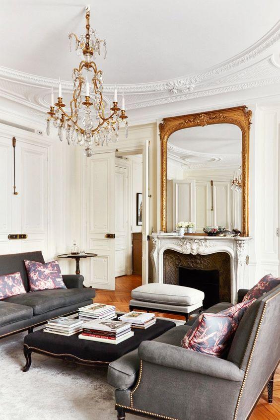 living room, wooden floor, white wall, white molding ceiling, crystal chandelier, grey sofas, dark grey ottoman, white molding fireplace, golden mirror, white rug