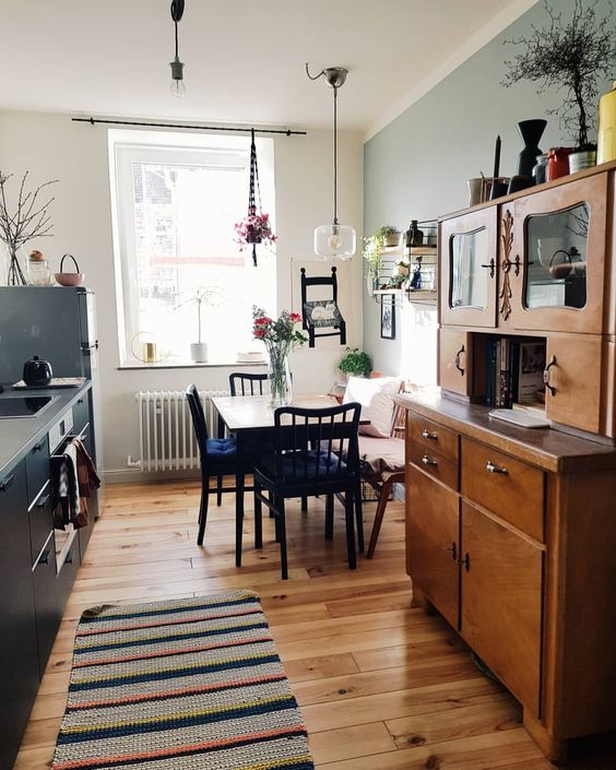 long small kitchen, wooden floor, soft pale wall, white wall, small dining set, clear glass pendant, wooden cabinet, grey kitchen cabinet