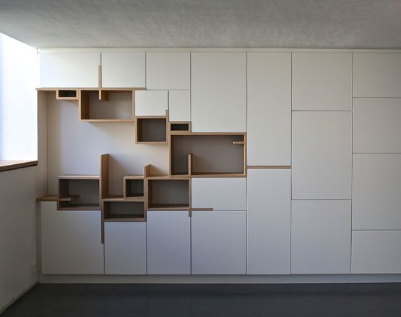long white cupboard with hole on the left filled with brown wooden shelves