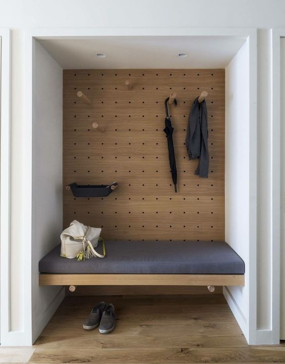 nook on the wall, pegboards on the deph, white wall, ceiling lamp, wooden floating bench, blue cushion, wooden floor
