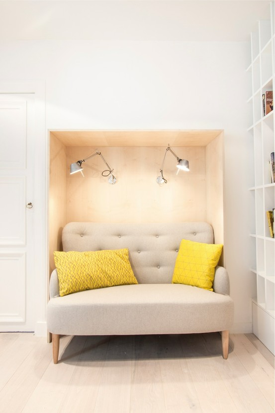 nook on the wall, wooden wall, sconce, sofa inside, yellow pillows, wooden floor, bookcase on the side