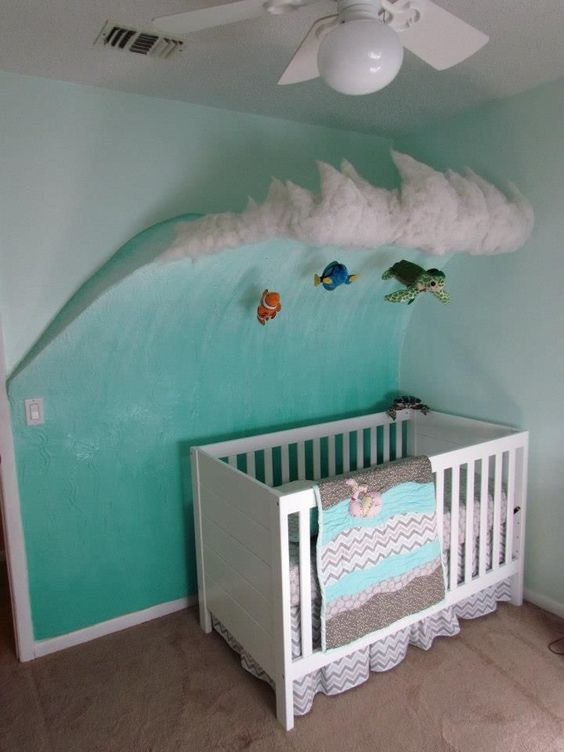 nursery with green wall with wave and surfers, white wooden crib, white ceiling fan