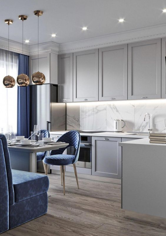 off white kitchen with upper and bottom cabinet, white marble backsplash, wooden floor, dining table with blue chairs and sofa, round golden pendants