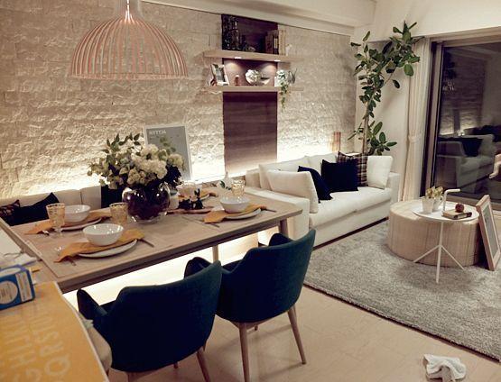 open living room, wooden floor, grey rug, white sofa, wooden table, blue chair, bamboo pendant, white stoned wall, floating shelves