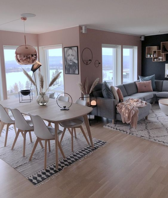 open living room, wooden floor, grey sofa, pillows, pink wall, pink golden pendant, wooden dining set, rug