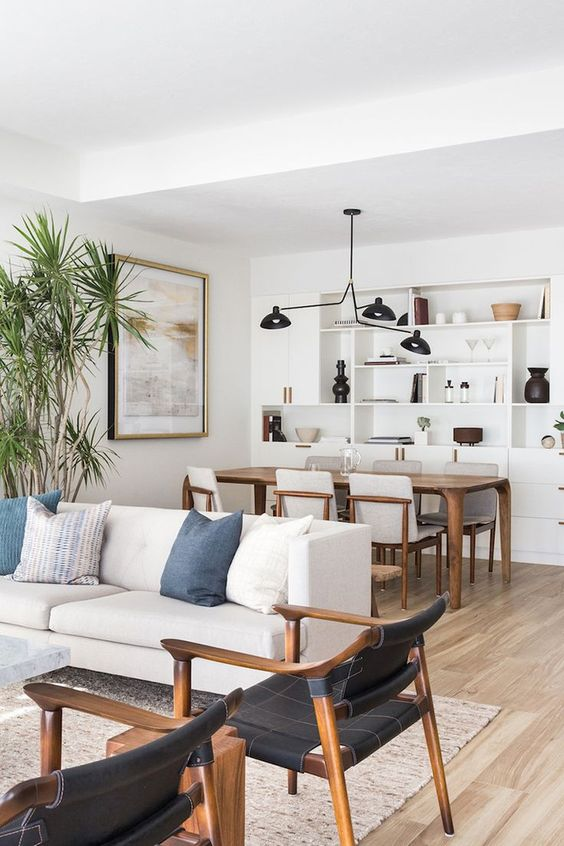 open room, dark wooden table, dark wooden chair with white cushion, dark woodenchairs with black leather, white sofa, pendant, built in white shelves
