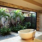 Outdoor Bathroom Ideas Acrylic Freestanding Bathtub Tub Filler Mosaic And Concrete Shower Walls Path Beige Floor Tile Palm Trees Stone Fence Sliding Doors Black Shower Fixtures