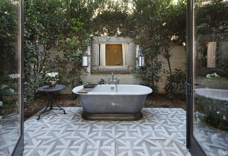outdoor bathroom ideas freestanding acrylic bathtub grey floor rile wall mirror plants black side table tub filler glass doors outdoor lighting