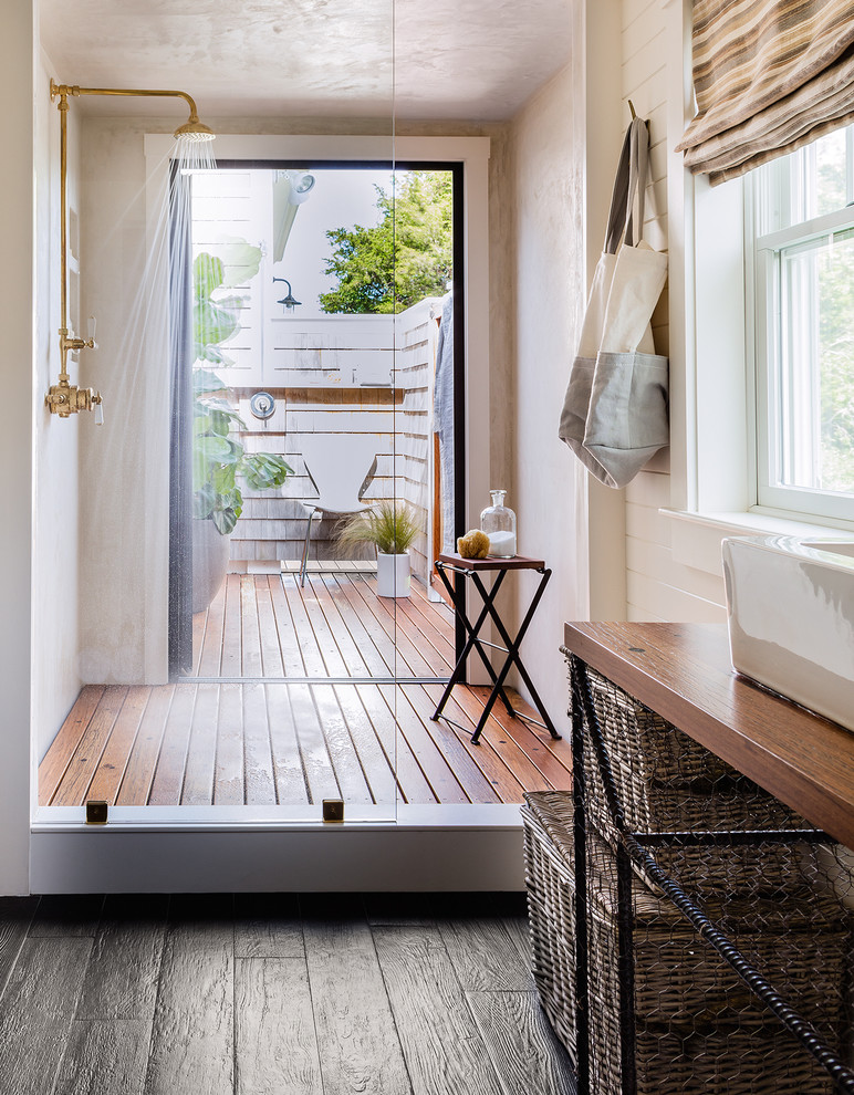 outdoor bathroom ideas wooden flooring glass wall white window shower head stool wink rattan basket black tile gold shower fixtures roman shade