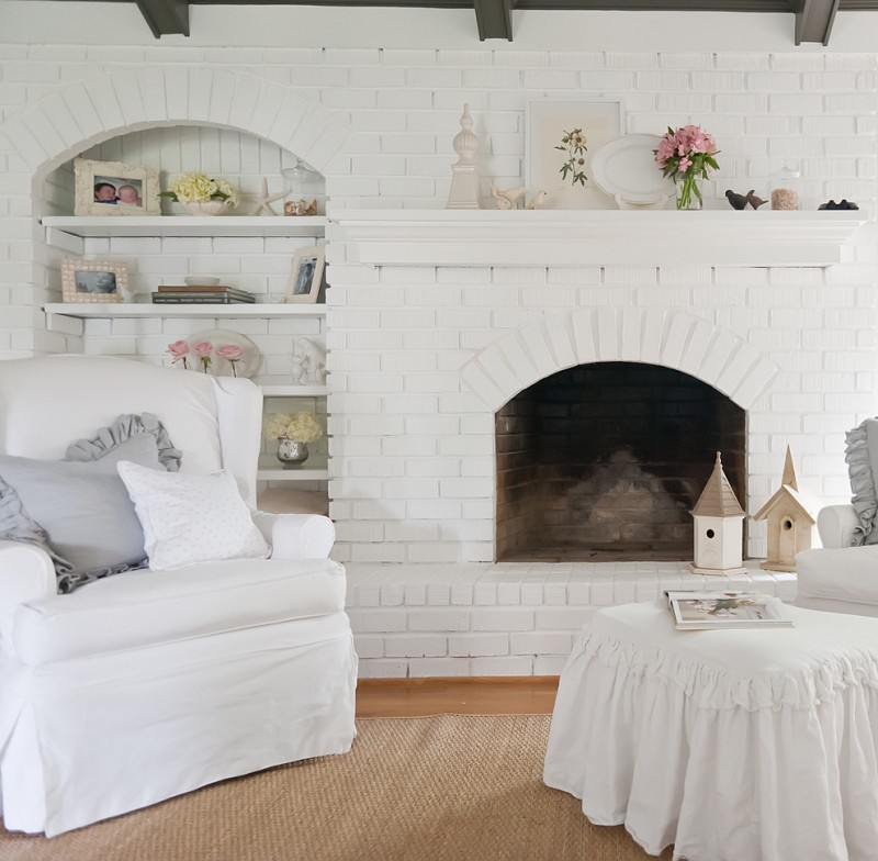 paint fireplace white brick wooden floor rattan rug white armchair white skirt lounge chair white built in shelves wood beams pillows