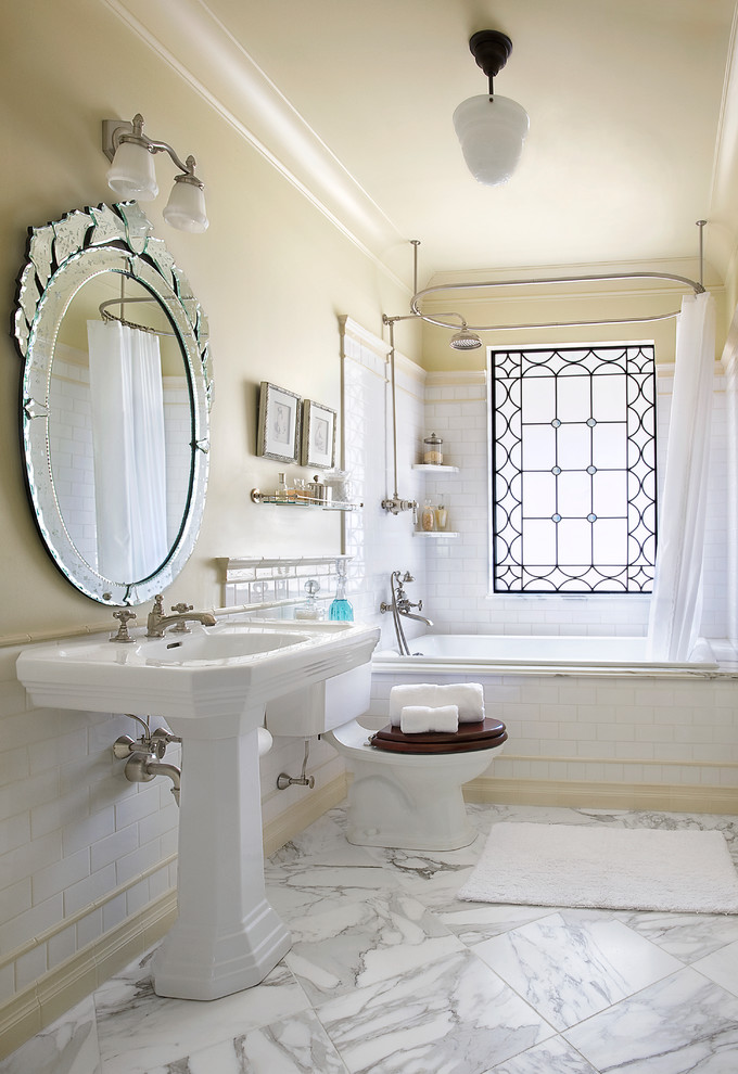pedestal bathroom vanity round wall mirror wall sconce white curtain window curtain rod shower head built in tub marble floor tile glass rack white subway tile