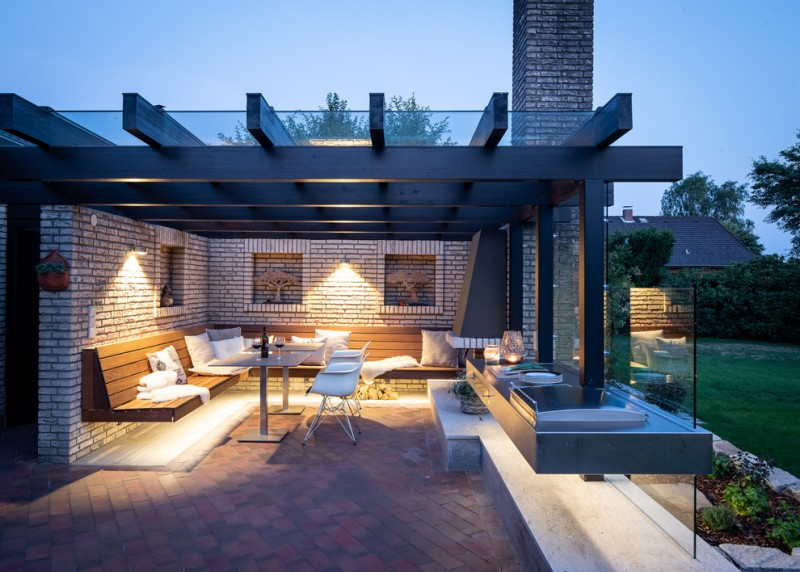 pergola on existing deck glass roof floating wooden bench with back white pillows square white pedestal tables white eames chairs glass walls fireplace wall sconces