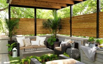 pergola on existing deck wooden privacy outdoor sofa and chairs grey coffee table ottoman beige cushions side table white pillows artificial grass rug plants