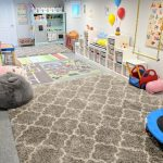 Playroom, Grey Floor, Grey Ruf, Interactive Rug, Grey Wall, White Wooden Shelves, Toys, Balloons, Grey Study Table