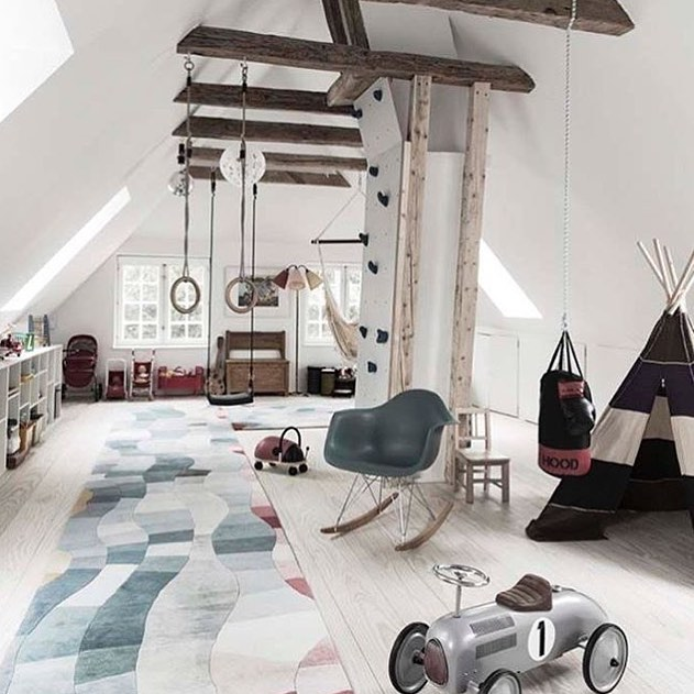 playroom, sloping ceiling, wooden floor, rug, toys, rocking chair, monkey bars, swing, wooden beams, hammock, tent, shelves