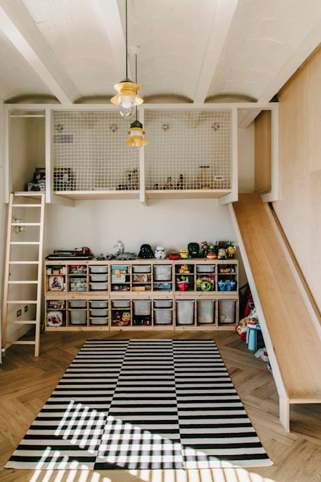 playroom, wooden floor, black white striped rug, wooden upstairs with stairs and slide, shelevs with boxes, toys