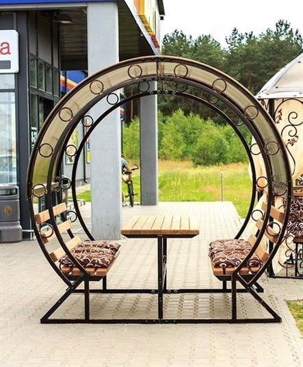 round curvy pergola with details, wooden table in the middle, bench on both ends