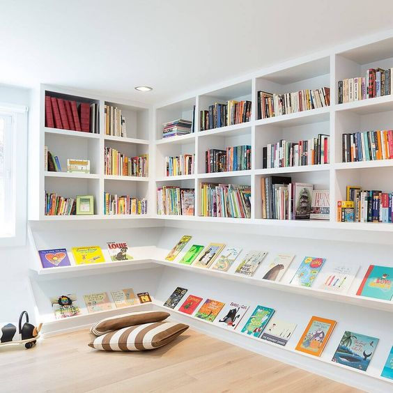sloping white wooden chelves, white bookshelves, wooden floor