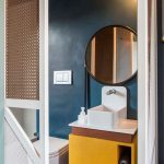 Small Bedroom, Blue Wall, Round Mirror, Yellow Cabinet, Small White Sink, White Floating Toilet, Rattan Partition