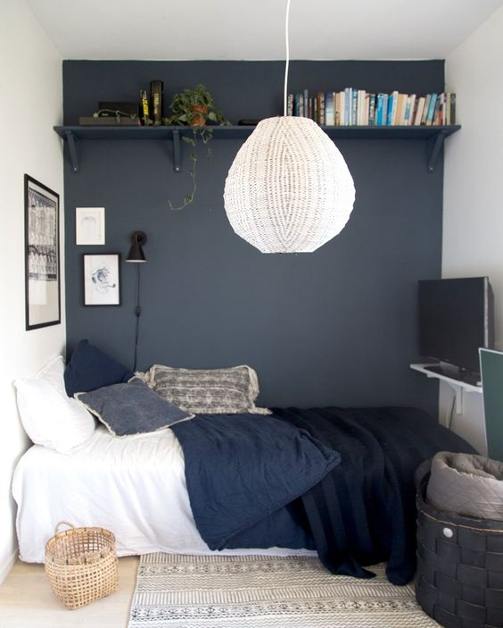 small bedroom for teen boy, navy statement wall with floating shelves, white pendant, wooden floor, rug, black basket, TV