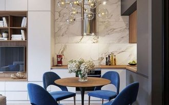 small corner kitchen, grey white cabinet, white marble wall, wooden top, woode  top tulip table, blue velvet chairs, bulubs pendant