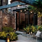 Small Garden, Grey Patio Floor, Metal Chairs With Details, Green Bush With Fairy Lights, Wooden Beams