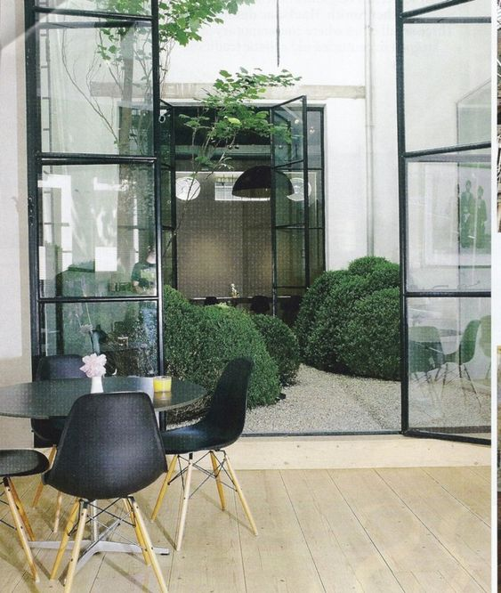 small indoor garden with bushes and a tree, glass doors, wooden floor, modern round table and chairs