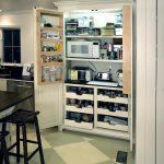 Small Kitchen Appliance Storage Door Cabiet Drawers Black Stools White Island Black Countertop Sink Dishwasher White Window Grren And Beige Floor Tiles