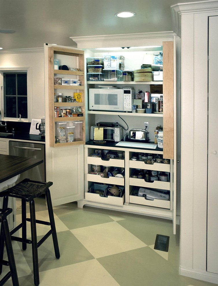 small kitchen appliance storage door cabiet drawers black stools white island black countertop sink dishwasher white window grren and beige floor tiles