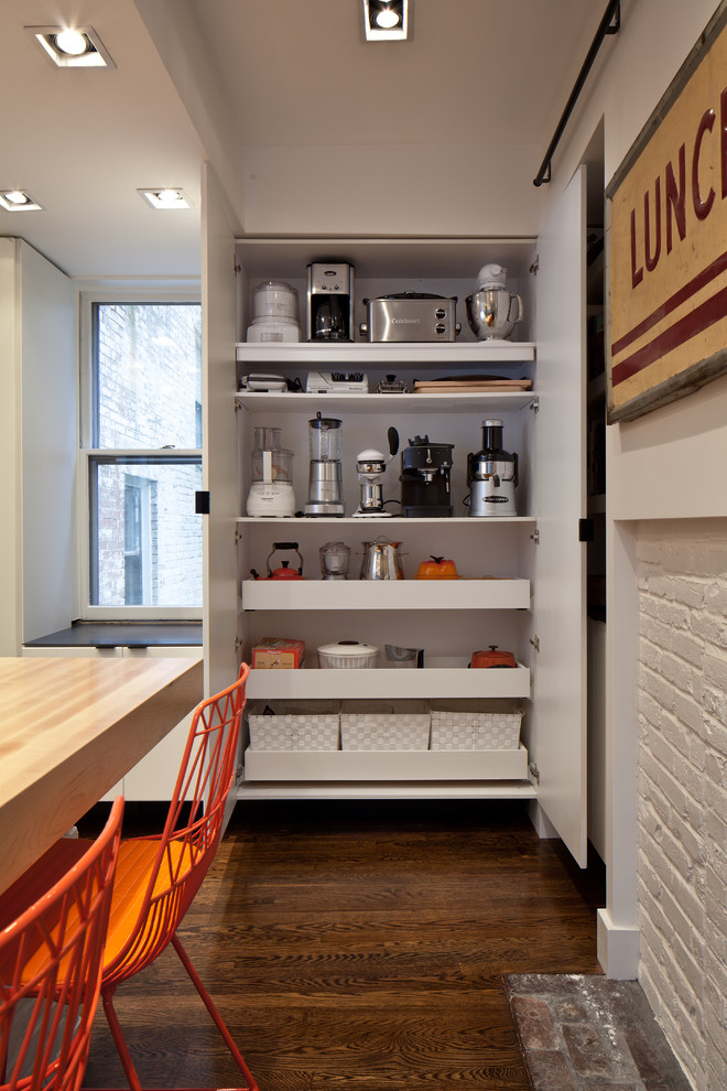 small kitchen appliance storage orange chair wooden table wooden floor toaster coffee maker white walls window white basket mixer blender juicer white wooden shelves