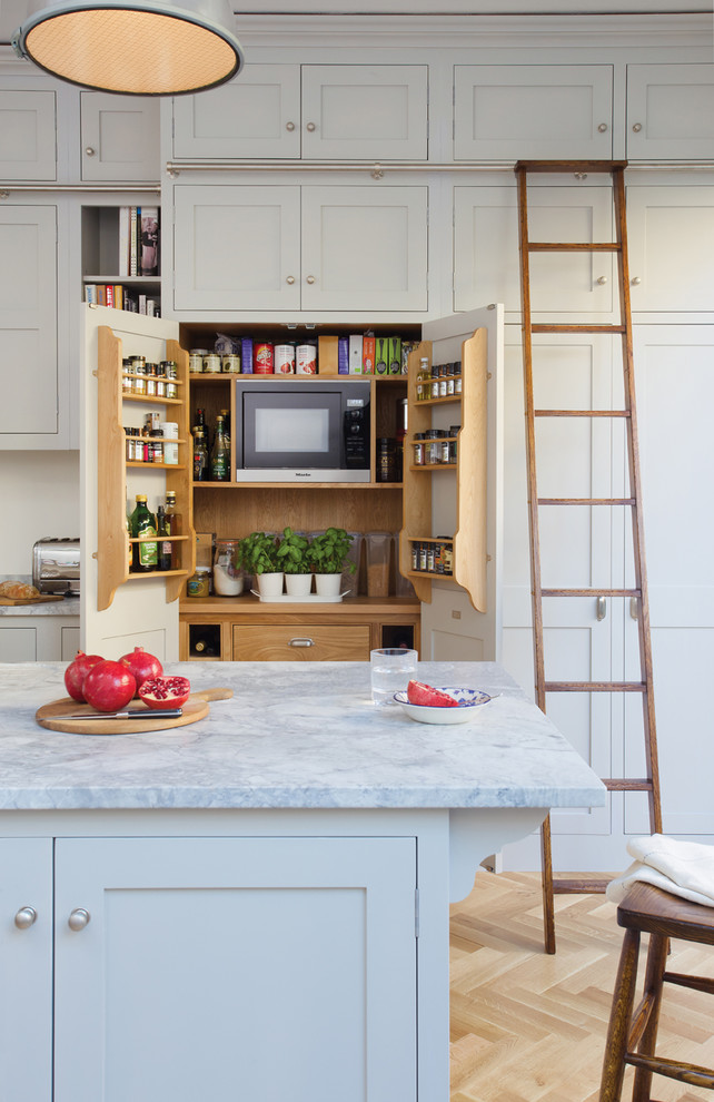 small kitchen appliance storage white cabinet white marble coountertop hidden shelves wooden ladder wooden stool white island microwave toaster bookshelves