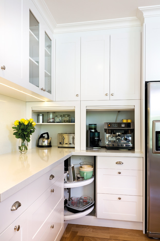 small kitchen appliance storage white cabinets white countertop refrigerator corner lazy susan storage drawers coffee maker teapot toaster glass cabinet door recess