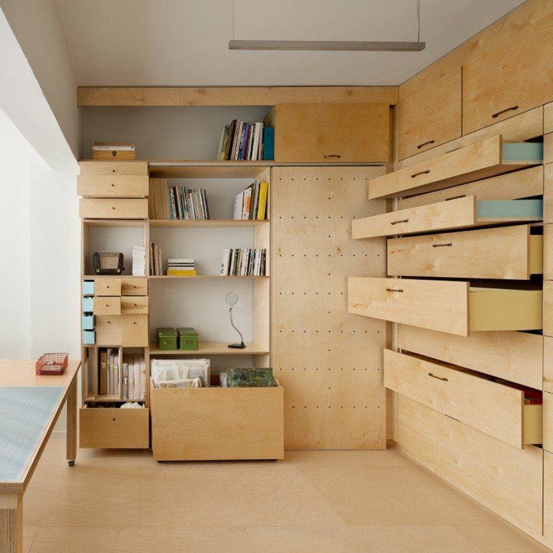small room with natural woof look built in cupboard with desk, shelves, drawers, pegboards, folding bed