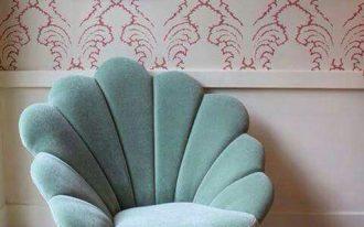 soft green velvet shell chair with rattan legs, wooden floor, rattan rug, white wainscoting, wallpaper