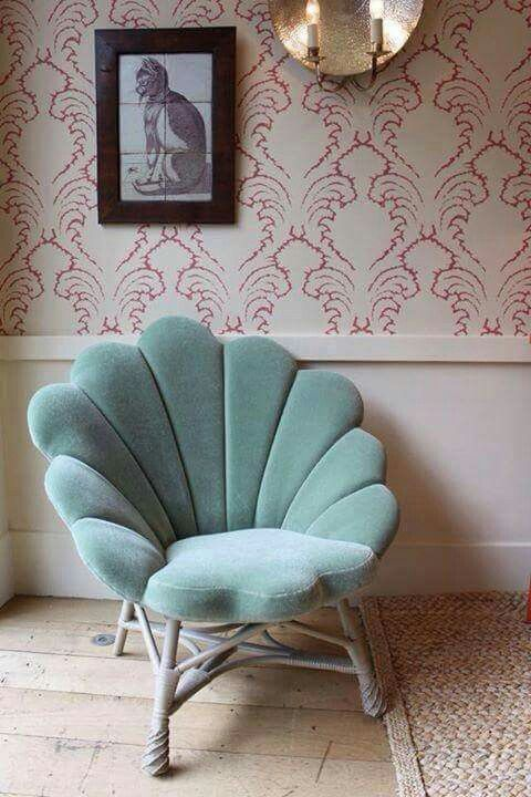 soft green velvet shell chair with rattan legs, wooden floor, rattan rug, white wainscoting, wallpaper