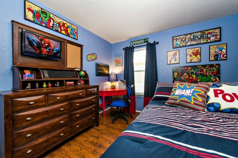 superhero room blue wall blue curtain wooden dresser wooden storage red desk blue chair window colorful bedding superhero wall decoration table lamp