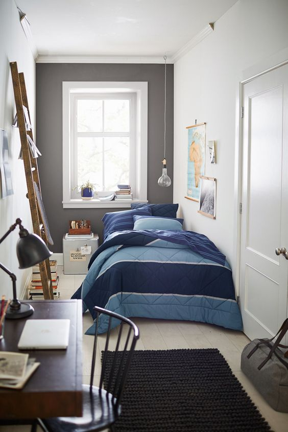 teen boy bedroom, wooden floor, white wall, wooden rail, blue bedding, grey statement wall with window, wooden table black chair, black rug